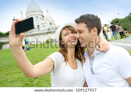 Lovers taking picture of themselves in front of Sacre Coeur