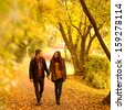 Lovers walking hand in hand in autumn park - stock photo