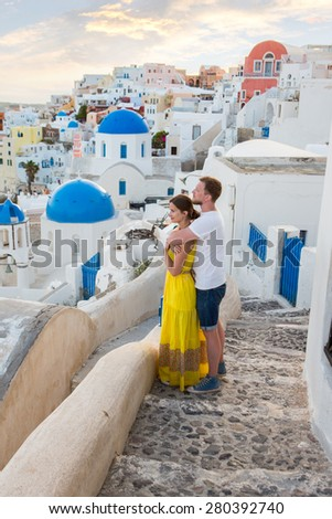 Lovers walking, hugging honeymoon on the most romantic island Santorini, Greece. Sunset in the city Oia. - stock photo