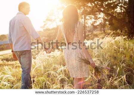 lovers walking in a field at sunset holding hands - stock photo