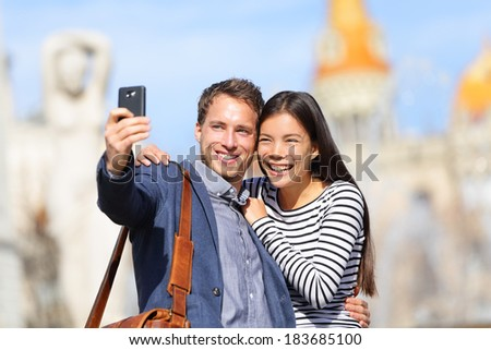 Lovers - young couple happy taking selfie photo with smart phone camera. Modern urban city man and woman having fun taking self portrait picture with smartphone, Catalonia Square, Barcelona, Spain - stock photo