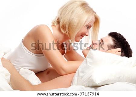 Loving affectionate heterosexual couple on bed. - stock photo