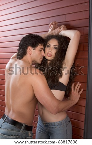 Loving affectionate nude heterosexual couple in affectionate sensual kiss. Mid adult Caucasian men in late 30s and young Latina woman in early 20s - stock photo