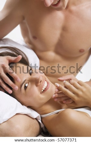 Loving affectionate nude heterosexual couple on bed. - stock photo