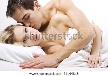 Loving affectionate nude heterosexual couple on bed in affectionate sensual kiss.