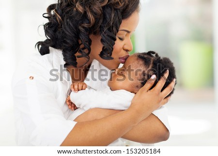 loving african american woman kissing her baby girl - stock photo