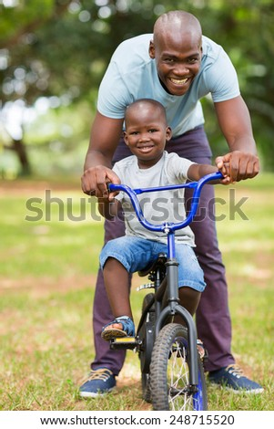 loving african father helping son ride a bike outdoors - stock photo