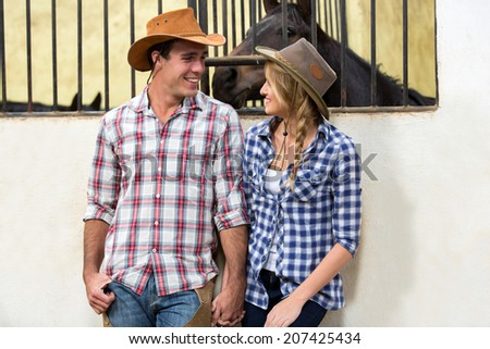 loving american western couple holding hands in stable - stock photo