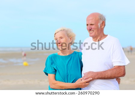 Loving amusing elderly couple enjoying the beach and sea breeze on sunny day - active healthy retirement concept - stock photo