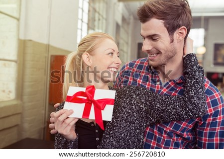 Loving attractive young blond woman thanking her husband for a gift tied in a large red bow for Valentines Day turning to smile into his eyes - stock photo