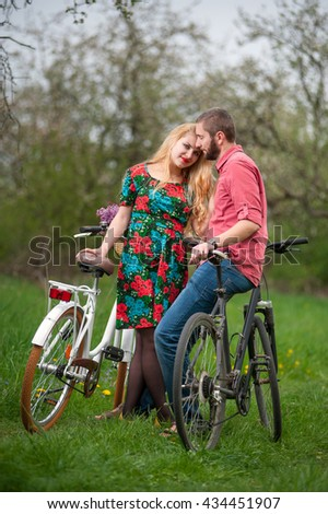 Loving beautiful couple with bicycles against the background of trees and fresh greenery in spring garden. Woman looking to the camera. Couple together enjoying romantic holidays