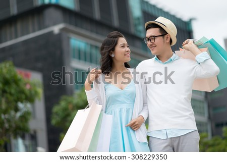 Loving beautiful couple with shopping bags standing outdoors - stock photo