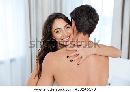 Loving beautiful woman hugging her husband and smiling at home - stock photo