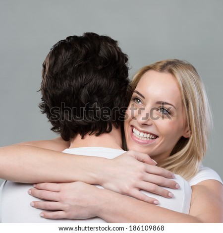Loving beautiful woman hugging her husband clasping him tightly as she looks over his shoulder with a wide joyful smile - stock photo