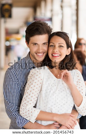 Loving beautiful young couple standing in a close intimate embrace smiling happily at the camera in an urban street