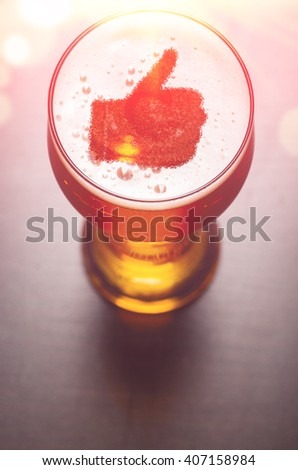 loving beer, thumb symbol on foam in glass on black table, view from above