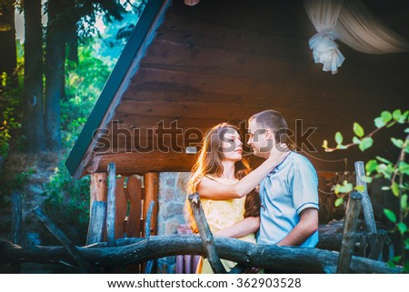 loving boy and girl standing near wooden house look at each other feeling of love relationships - stock photo