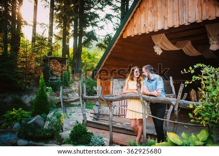 loving boy and girl standing near wooden house look at each other through the trees sunlight feelings of love relationships - stock photo