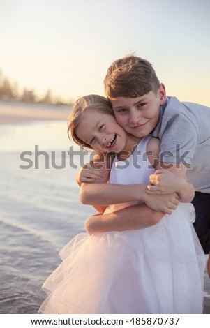 Loving brother and sister on the beach, toning