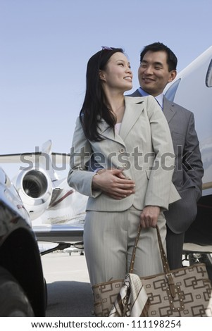Loving business couple standing together on airfield - stock photo
