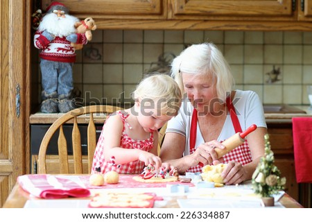 Loving caring grandmother, beautiful senior woman, baking tasty christmas cookies together with her granddaughter, cute little toddler girl, sitting at the table in classic traditional wooden kitchen