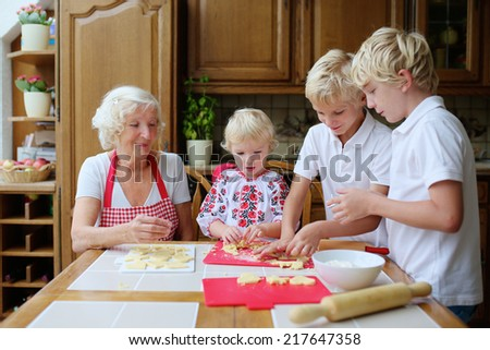Loving caring grandmother, beautiful senior woman, baking tasty sweet cookies together with her grandchildren, cute little girl and two boys, sitting at the table in classic traditional wooden kitchen - stock photo