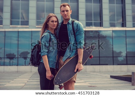 loving casual couple posing over glass building.