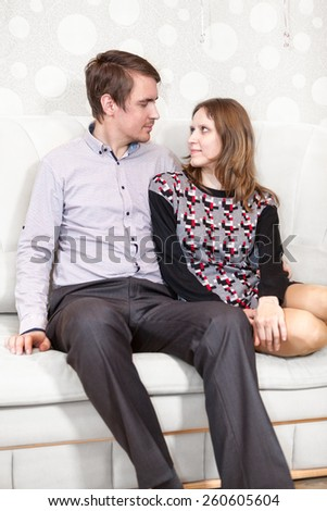 Loving Caucasian couple looking at each other while sitting sofa - stock photo