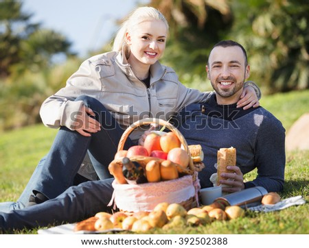 Loving cheerful young couple chatting as having picnic in sunny day  - stock photo