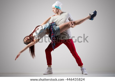 Loving cool casual couple dancing. 2 modern style beautiful dancers working out. Beautiful pair of lovers passionate dance practice. Full length image, studio gray background - stock photo