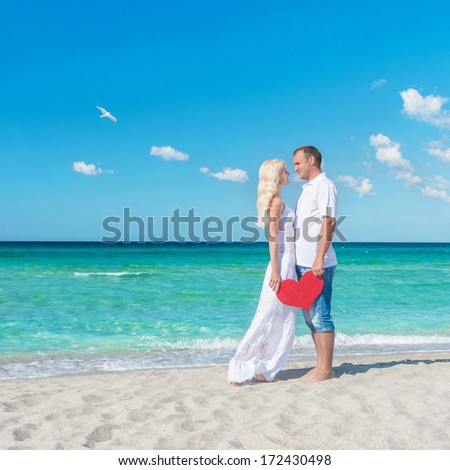 Loving couple at sunny sea beach with red heart - St.Valentines Day concept - stock photo