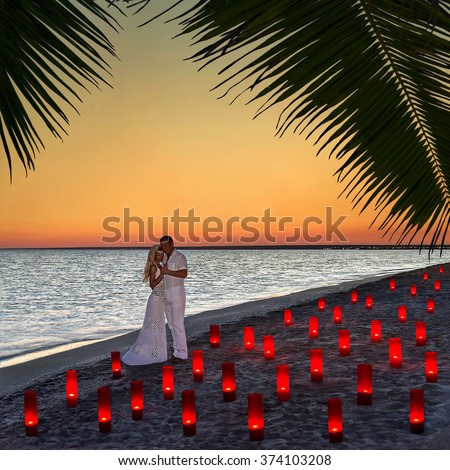 Loving couple at tropical ocean beach in many red magic candle lights against sunset - St.Valentines Day, Wedding, Proposal or Honeymoon romantic concept - stock photo