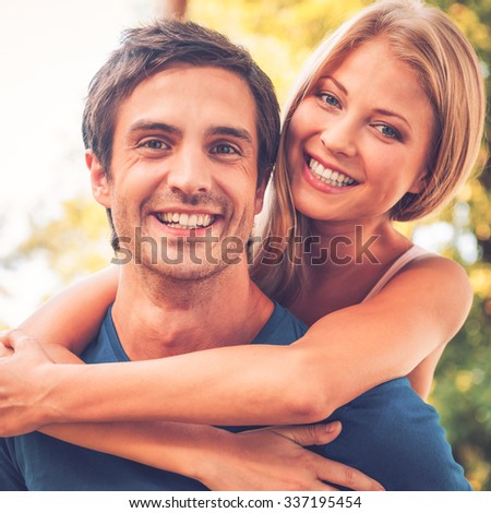 Loving couple. Beautiful young loving couple standing outdoors together while woman hugging her boyfriend and smiling - stock photo