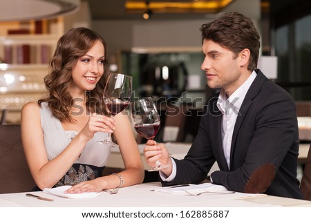 Loving couple celebrating at the restaurant. Looking happy and romantic