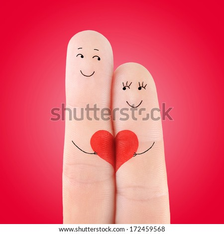 loving couple concept with big valentine heart, painted at fingers against red