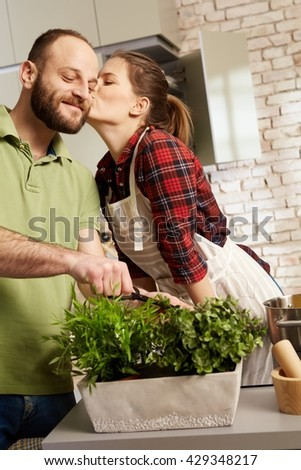 Loving couple cooking together in kitchen, kissing.