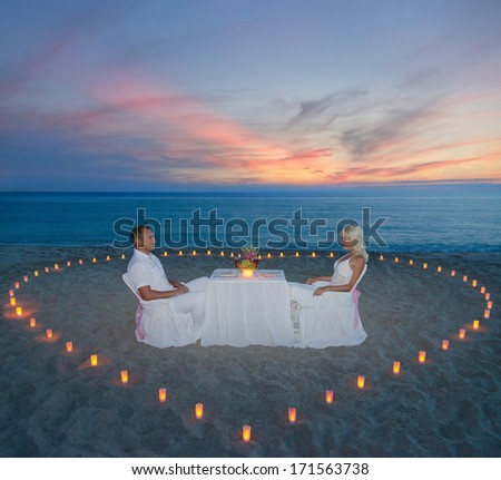 Loving couple during romantic dinner with heart of candles on tropical sandy sea beach