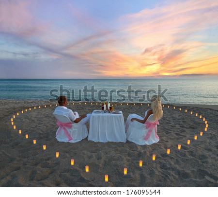Loving couple during romantic dinner with heart of candles on tropical sandy sea beach - stock photo