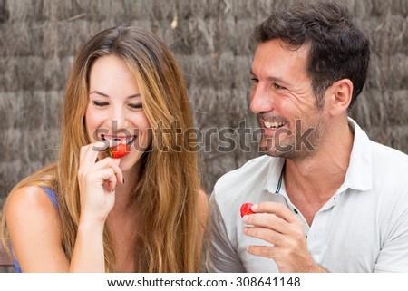 Loving couple eating strawberries - stock photo