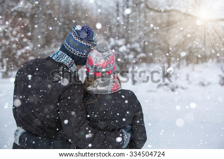 Loving couple embracing in winter park. They put colored caps and scarves. Loving couple turned away from the camera. Copy space. The girl hat with red hearts. - stock photo