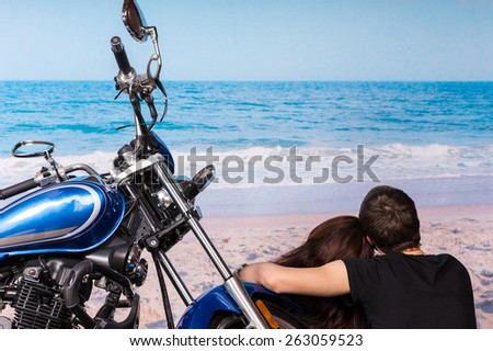 Loving couple enjoying a quiet day at the seaside sitting alongside their motorbike facing out over the ocean and waves on the golden sand