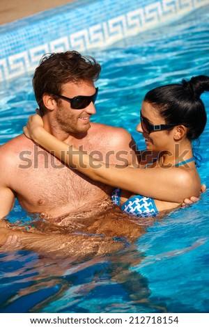 Loving couple enjoying summer holiday in swimming pool, smiling. - stock photo
