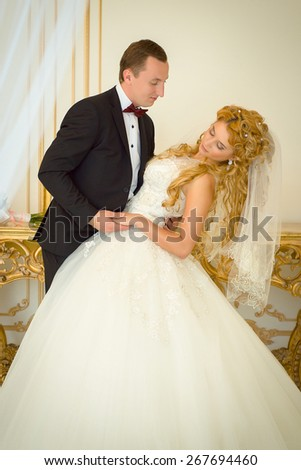 Loving couple groom and bride posing in a posh hotel room