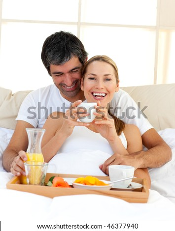 Loving couple having breakfast lying in the bed at home