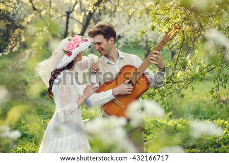 Loving couple having fun in the blossoming apple garden and  playing guitar. Spring,  Retro stile. emotions.
