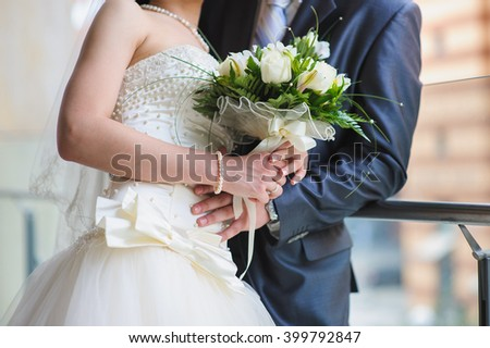 Loving couple holding a bouquet of white roses flowers. Groom in a gray suit and hugging woman. Bride with ring and bracelet of pearls on a hand holding bouquet. wedding dress with a large white bow.