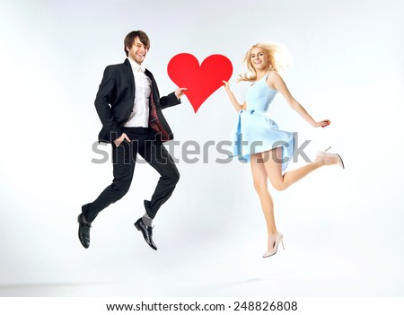 Loving couple holding a heart symbol - stock photo