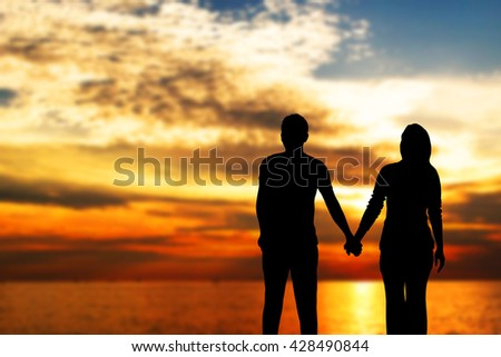 Loving couple holding hands at sunset. - stock photo