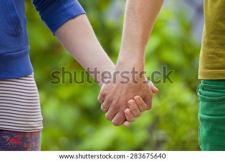 Loving couple holding hands of each other on nature - stock photo