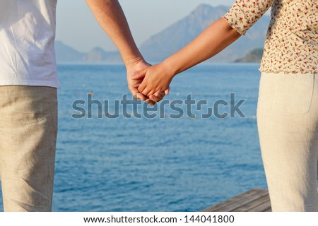 Loving couple holding hands on the background of the sea